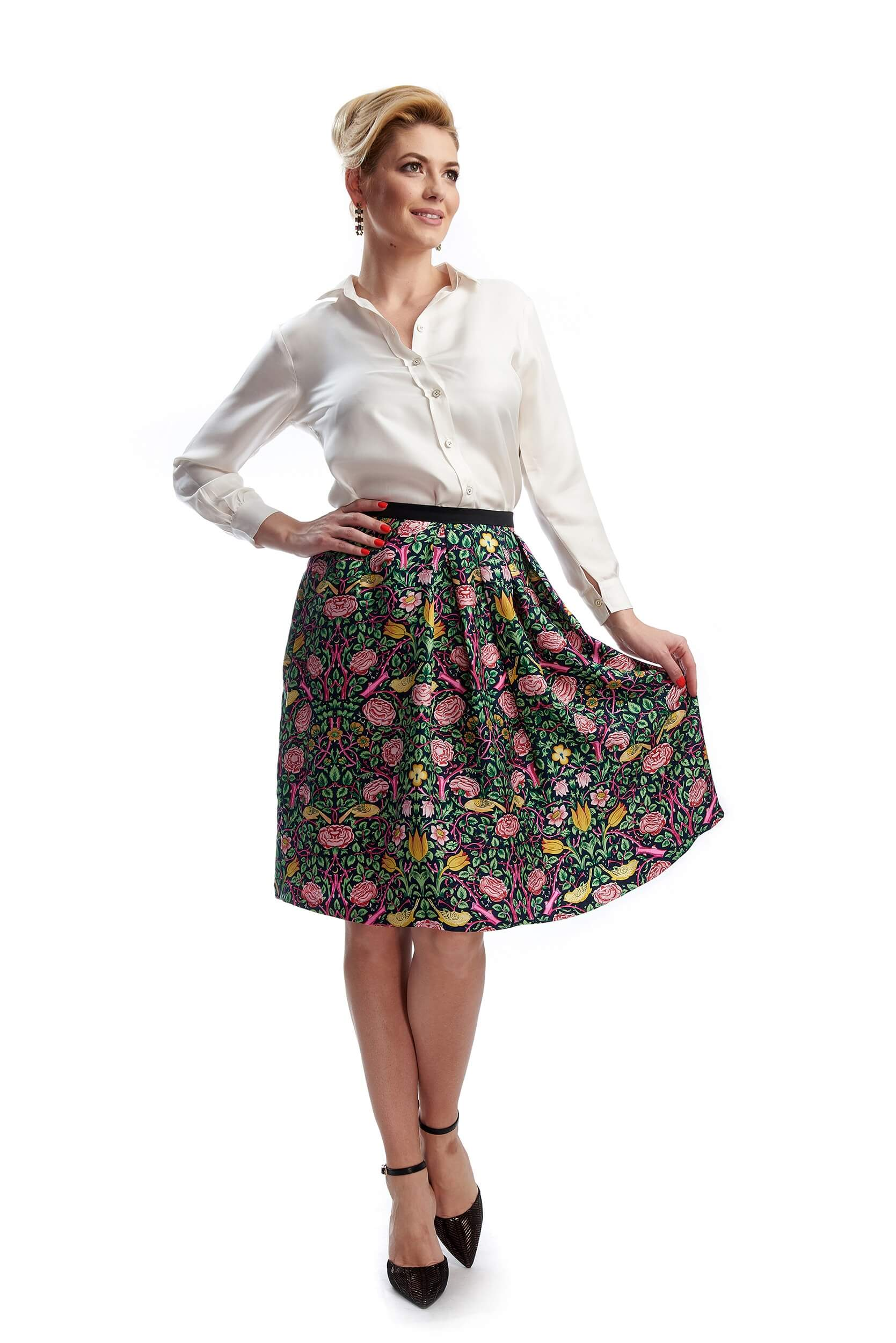 Woman showing the pleats of the Amélie silk twill skirt with floral print
