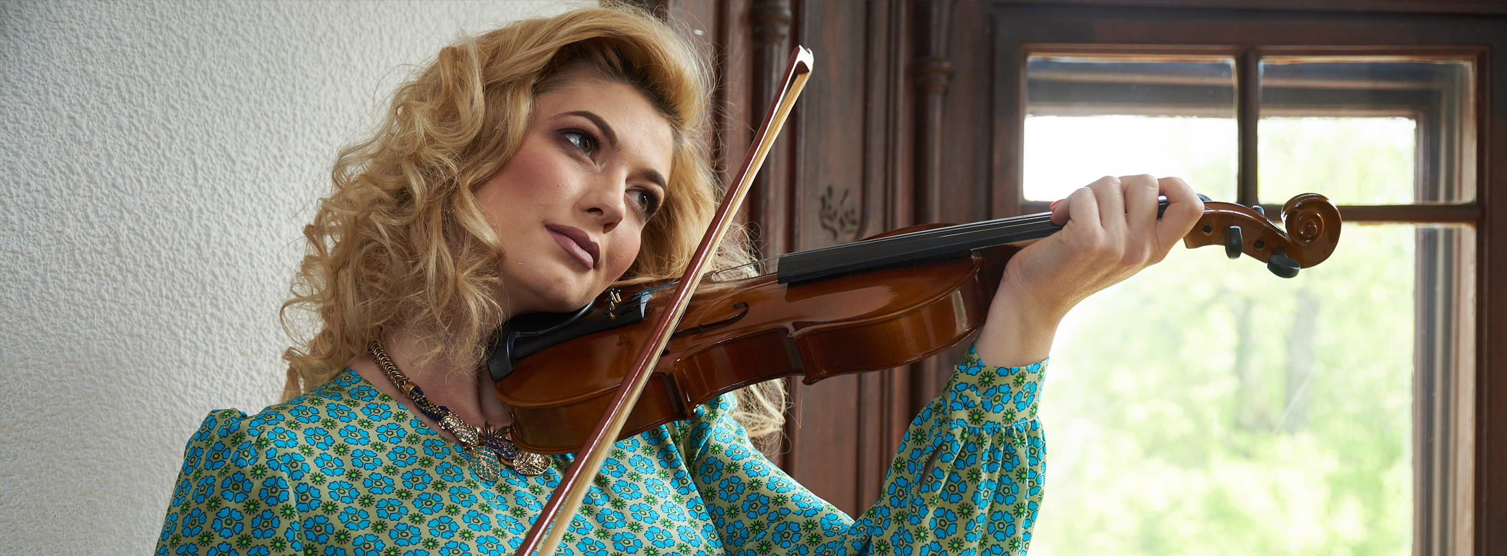 Woman wearing the Brigitte silk crepe jumpsuit with floral print and playing the violin